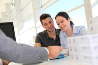 Couple in real-estate agency signing property loan contract