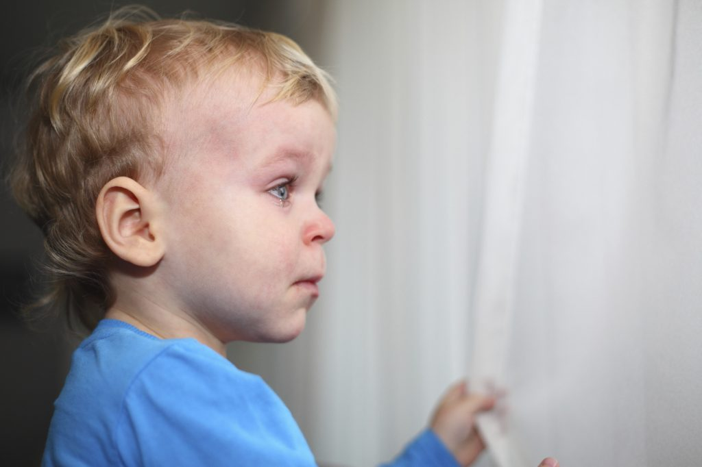 Cute little Caucasian boy standing looking through window holding onto drapes and crying. Teary eyes of a little boy.